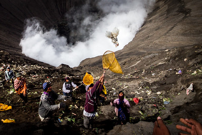 A chicken is thrown into the crater of Mt Bromo - an offering to the volcano god. The catchers eagerly await.