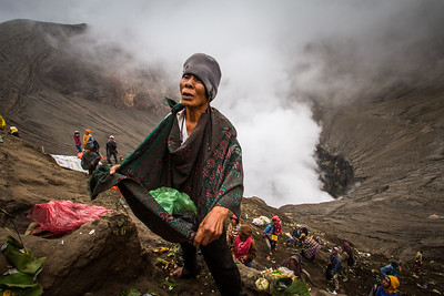 Tengger people pray to the god of the volcano before throwing their offering into Mount Bromo's smoking crater.