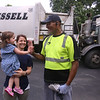 Vivienne Culhane, 2, and her mother Meghan Culhane, of Dracut greet Mike Lewis of Dorchester, the driver on their trash & recyling route. It was his last week in Dracut, because the town has switched to a new contractor. (SUN/Julia Malakie)