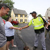 From left, Patrick Culhane of Dracut, and his mother-in-law Dale Pelletier of Windham, N.H., say goodbye to Mike Lewis of Dorchester, the driver on Culhane's trash & recyling route. At rear are Meghan Culhane and daughter Vivienne, 2. It was Lewis' last week in Dracut, because the town has switched to a new contractor. (SUN/Julia Malakie)