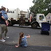 Sisters Evelyn, 3, right, and Vivienne Culhane, 2, and their mother Meghan Culhane, of Dracut, wave goodbye to Mike Lewis of Dorchester, the driver on their trash & recyling route. It was his last week in Dracut, because the town has switched to a new contractor. (SUN/Julia Malakie)