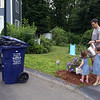 Sisters Evelyn, 3, and Vivienne Culhane, 2, and their father Patrick Culhane, of Dracut, water flowers while they wait to say goodbye to Mike Lewis of Dorchester, the driver on their trash & recyling route. It was his last week in Dracut, because the town has switched to a new contractor. (SUN/Julia Malakie)
