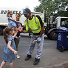 Sisters Evelyn, 3, front, and Vivienne Culhane, 2, along with their mother Meghan Culhane, of Dracut, visit with Mike Lewis of Dorchester, the driver on their trash & recyling route. It was his last week in Dracut, because the town has switched to a new contractor. (SUN/Julia Malakie)