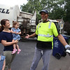 Sisters Evelyn, 3, left, and Vivienne Culhane, 2, along with their mother Meghan Culhane, of Dracut, say goodbye to Mike Lewis of Dorchester, the driver on their trash & recyling route. It was his last week in Dracut, because the town has switched to a new contractor. (SUN/Julia Malakie)