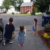 Sisters Evelyn, 3, right, and Vivienne Culhane, 2, and their mother Meghan Culhane, of Dracut, wait to greet Mike Lewis of Dorchester, the driver on their trash & recyling route. It was his last week in Dracut, because the town has switched to a new contractor. (SUN/Julia Malakie)