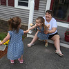 Sisters Evelyn, 3, center, and Vivienne Culhane, 2, left, and memere (grandmother) Dale Pelletier of Windham, N.H., wait to say goodbye to Mike Lewis of Dorchester, the driver on their trash & recyling route. It was his last week in Dracut, because the town has switched to a new contractor. (SUN/Julia Malakie)