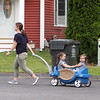 Sisters Evelyn, 3, and Vivienne Culhane, 2, get a wagon ride around their cul-de-sac with their mother Meghan Culhane of Dracut as the wait for the arrival of Mike Lewis of Dorchester, the driver on their trash & recyling route. It was his last week in Dracut, because the town has switched to a new contractor. (SUN/Julia Malakie)