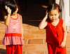 Two Vietnamese girls on a sidewalk somewhere in a Mekong River Delta town, probably in Ving Long province