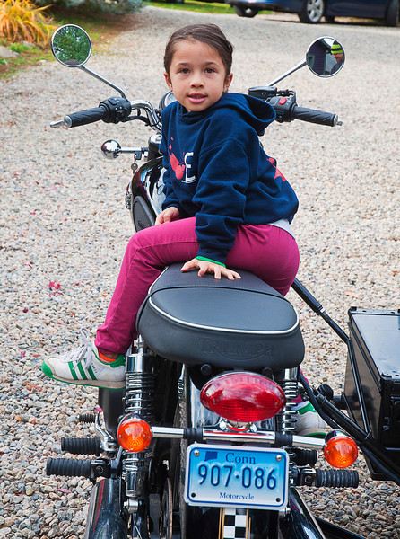 """Emma rode in the Ural side car on her dad's Triumph Bonneville T100.<br /> <br /> While he shopped our tag sale, she and I discussed hawks and the difference between fiction and non-fiction; I estimate her age to be six going on thirty.<br /> <br /> You can see the bike better here:  <a href=""""http://tinyurl.com/l4nxuwm"""">http://tinyurl.com/l4nxuwm</a>"""