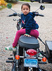 "Emma rode in the Ural side car on her dad's Triumph Bonneville T100.<br /> <br /> While he shopped our tag sale, she and I discussed hawks and the difference between fiction and non-fiction; I estimate her age to be six going on thirty.<br /> <br /> You can see the bike better here:  <a href=""http://tinyurl.com/l4nxuwm"">http://tinyurl.com/l4nxuwm</a>"