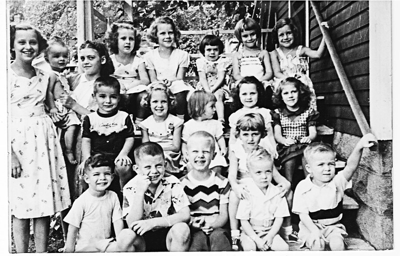 Every kid in my neighborhood when I was in first grade. I'm the one in the first row with a widow's peak picking my teeth. My best friend Bill is beside me in the wavy-striped shirt. My sister is the tiniest kid in the top row at the back. She was about two at the time.