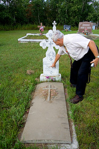 Ron Rosychuk reading a Ukrainian headstone