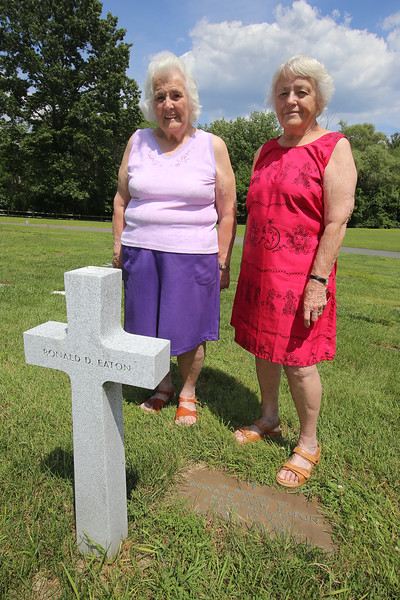 Joyce Dalton of Wilmington, left, and her sister Verlie Quinan of Centerville, Cape Cod, at their brother's gravestone at Wildwood Cemetery in Wilmington. Their brother, US Navy Ens. Ronald Dow Eaton, was missing in action in Korea, and his body was never recovered. (SUN/Julia Malakie)