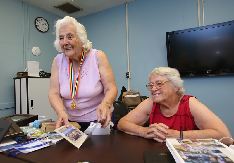 Joyce Dalton of Wilmington, left, and her sister Verlie Quinan of Centerville, Cape Cod, with gifts from their trip to South Korea as guests of the Korean War Veterans Revisit Korea Program. Their brother, US Navy Ens. Ronald Dow Eaton, was missing in action in Korea, and his body was never recovered. (SUN/Julia Malakie)