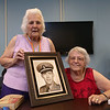 Joyce Dalton of Wilmington, left, and her sister Verlie Quinan of Centerville, Cape Cod, with a framed photo of their late brother, from their trip to South Korea as guests of the Korean War Veterans Revisit Korea Program. Their brother, US Navy Ens. Ronald Dow Eaton, was missing in action in Korea, and his body was never recovered. (SUN/Julia Malakie)