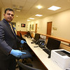 Lowell Community Health Center pediatrician Rajesh Kumble, M.D., of Andover, at the pediatrics department. Computer stations are set apart. They will be reopening first with infants, to get them caught up on vaccinations, and with only two patients at a time, one down each corridor.  (SUN/Julia Malakie)