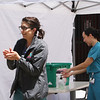 LCHC laboratory supervisor Lindsey Roberts of Amesbury, left, and chief of dental Sam Jordan of Arlington, disinfect their hands after removing gloves and mask after a session of COVID-19 testing at the tent outside Lowell Community Health Center. (SUN/Julia Malakie)