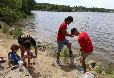 Rotha Proeung of Methuen fishes at Lake Mascuppic in Tyngsboro with his son Vairsna Proeung, 15, right, and daughter Savy Proeung, 19, and Savy's son Messiah Cruz, 2, all of Lowell. (SUN/Julia Malakie)