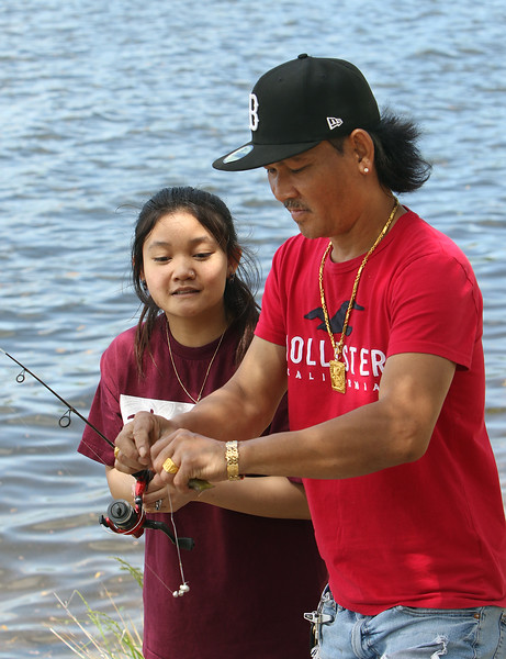 Rotha Proeung of Methuen fishes at Lake Mascuppic in Tyngsboro with his daughter Soriha Proeung, 17, of Lowell, who'd just caught a sunfish. (SUN/Julia Malakie)
