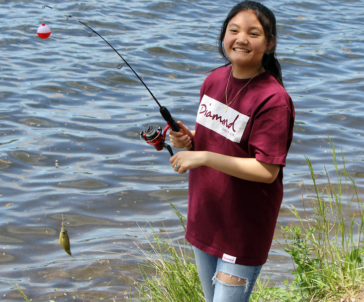 Soriha Proeung, 17, of Lowell, fishing with her father and siblings at Lake Mascuppic in Tyngsboro, holds up a sunfish she'd just caught. (SUN/Julia Malakie)