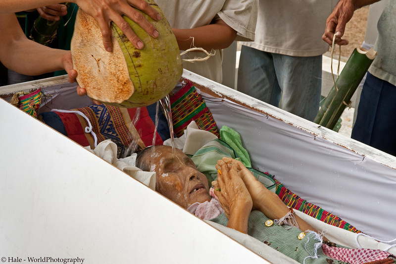 Family Member Pouring Green Coconut Water On Corpse's Face to Nourrish the Spirit On Its Journey