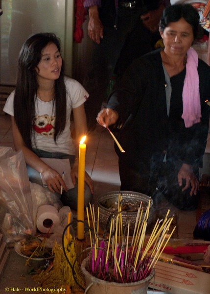 A Candle Is Lit and Incense Burned As Offerings As Deceased Woman's Daughter Looks On