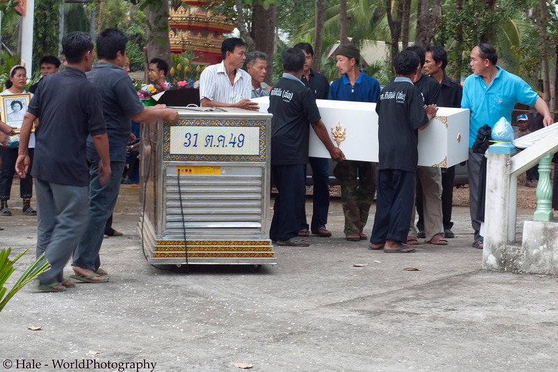 Family Members Removing Coffin From Rented Refrigerated Container