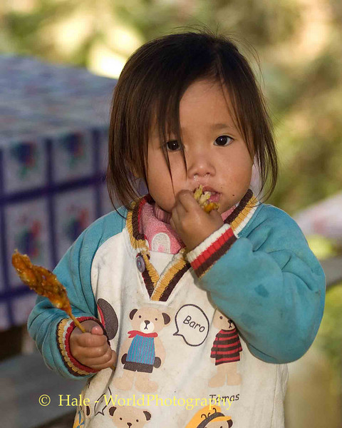 Young Hmong Girl Eating Chicken, Luang Prabang Laos