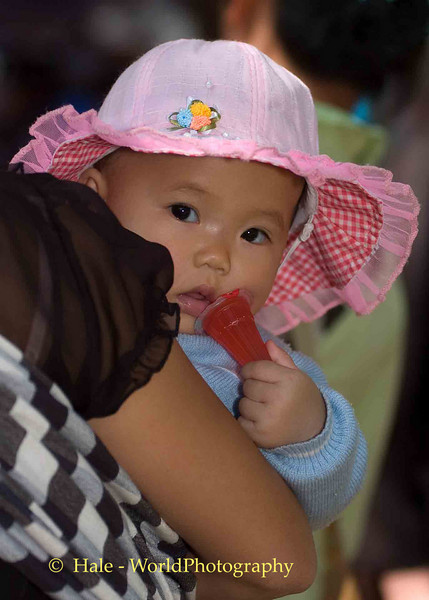 Baby With Snack at Hmong New Year Festival in Luang Prabang, Laos