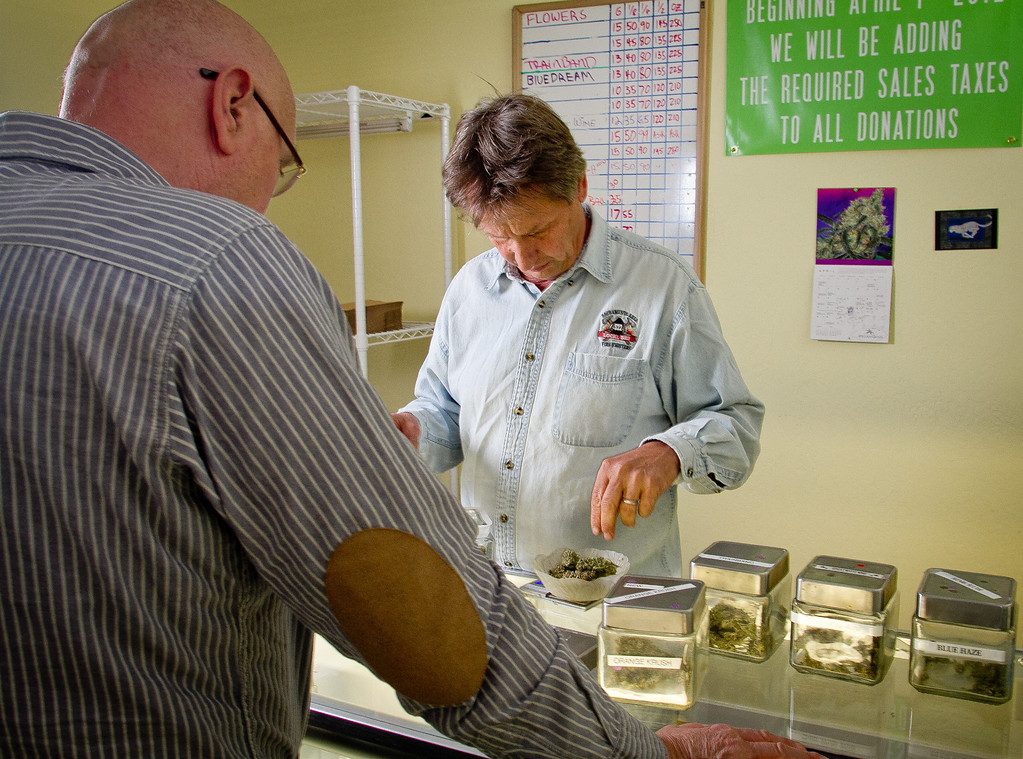 Lawrence Pebbles weighs out some Marijuana for a patient at his medical marijuana dispensary in Novato, Calif. on April 26th, 2012.