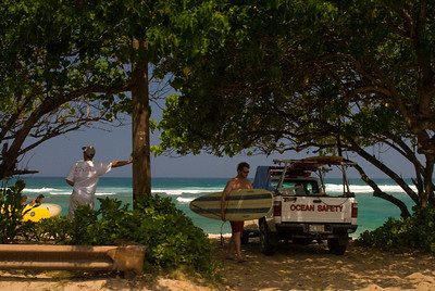 Laniakea Beach Surfers carrying their boards, coming from the ocean. Lifeguard truck on the sand North Shore of O'ahu, Hawai'i