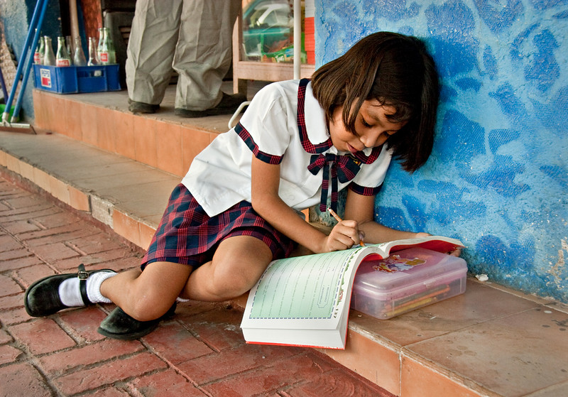 Little girl doing her homework on the steps of her father's shop