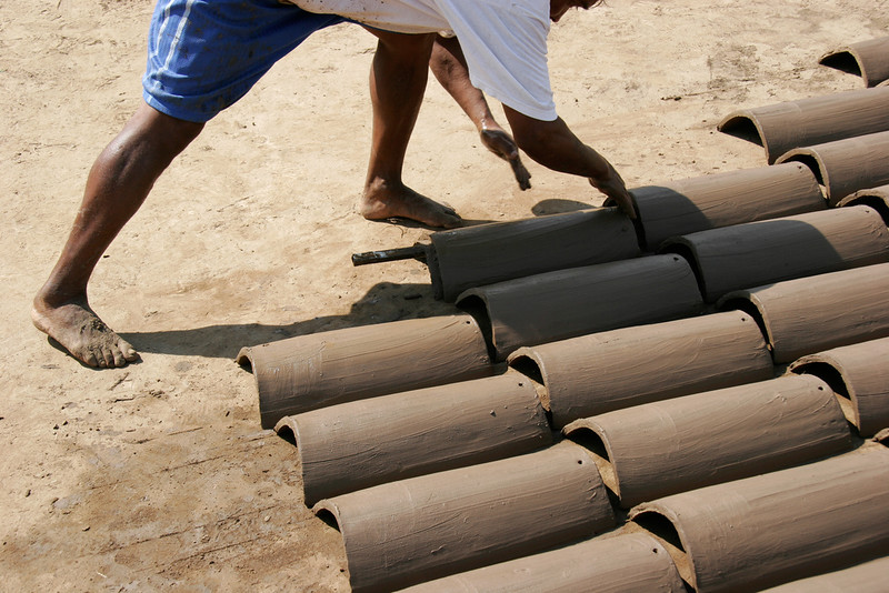 Hand making roofing tiles from clay