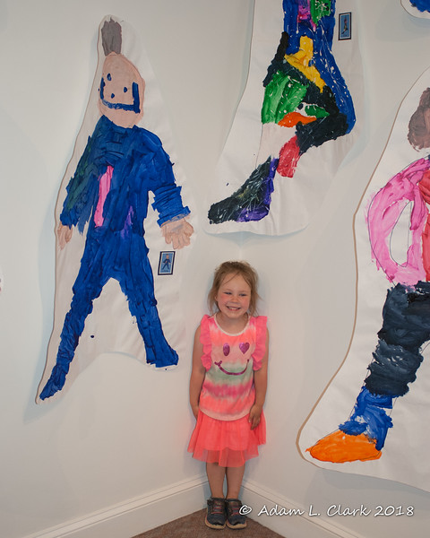 Liliana standing next to her self portrait (the blue one)