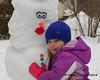 Liliana hugging her snowman