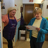 Littleton Meals on Wheels volunteer Jane Lyons, right, gets her list of addresses from Gayle Dalton of Medway, at the Council on Aging. Dalton is diner coordinator with Minuteman Senior Services, which prepares the meals.  (SUN/Julia Malakie)