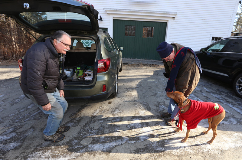 Volunteer Rick Findlay of Littleton, left, greeting Inga, a three-year-old viszla, who'd been for a walk with her owner Mark Conlon of Littleton, at Prouty Woods. He's involved with the New England Forestry Foundation, open space preservation, and fighting invasive species.(SUN/Julia Malakie)