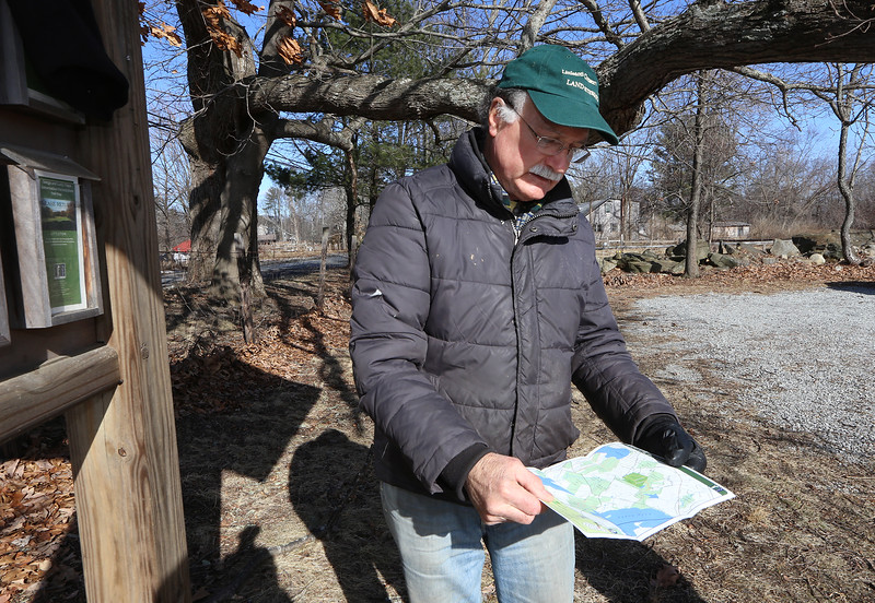 Volunteer Rick Findlay of Littleton, with the trail map he keeps stocked at the George & Lucy Yapp Conservation Land. He's involved with the New England Forestry Foundation, open space preservation, and fighting invasive species. (SUN/Julia Malakie)