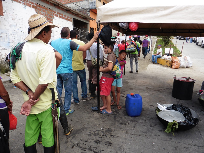 Protesters await breakfast being prepared in the street by supportive locals.