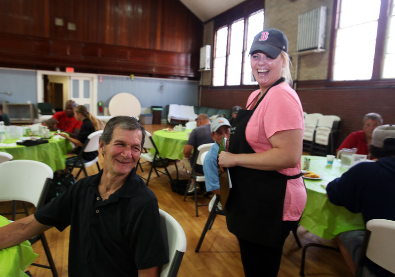 Raegan  Downs of Lowell, right, a volunteer at Living Waters Center of Hope, on Kirk Street in Lowell, collects names of people who wanted to get haircuts from another volunteer this weekend, including Edward Doyle of Lowell, left. (SUN/Julia Malakie)