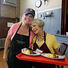 Raegan  Downs of Lowell, left, a volunteer at Living Waters Center of Hope, on Kirk Street in Lowell, with fellow volunteer Leanne George of Lowell, who was serving breakfasts. (SUN/Julia Malakie)