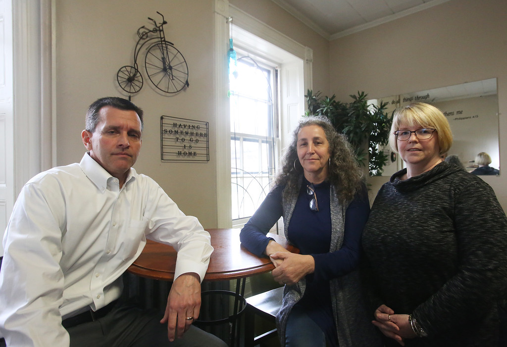 . From left, olunteer Tom Skahen of Westford, a board member of Living Waters, with executive director Diane Waddell of Chelmsford and volunteer Peggy Tripodi of Billerica, at the Living Waters office and cafe in downtown Lowell. (SUN/Julia Malakie)