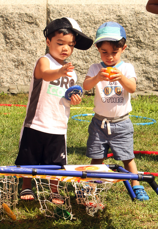 . Features at Friday afternoon Lowell Farmers Market. Maddox Chak, left, and Adam Al Maliki, both 2 and of Lowell, play with a bean bag toss game. (SUN/Julia Malakie)