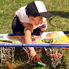 Features at Friday afternoon Lowell Farmers Market. Maddox Chak, 2, of Lowell, plays with a bean bag toss game. (SUN/Julia Malakie)