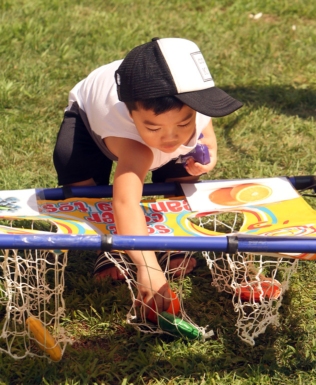 . Features at Friday afternoon Lowell Farmers Market. Maddox Chak, 2, of Lowell, plays with a bean bag toss game. (SUN/Julia Malakie)