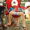 Features at Friday afternoon Lowell Farmers Market. Aizen Yim, 7, of Lowell, hangs out while his grandmother was busy. (SUN/Julia Malakie)
