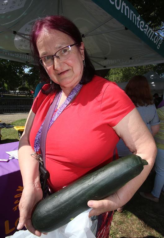 . Features at Friday afternoon Lowell Farmers Market. Fauna Rosenbloom of Lowell, with a large zucchini from the Dunbarton Farm booth that she got for $2 and plans to slice and cook. (SUN/Julia Malakie)