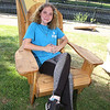 Features at Friday afternoon Lowell Farmers Market. Bianka Close, 18, of Lowell, who is a culinary student with YouthBuild, sits in one of the Adirondack chairs that YouthBuild sells. Plain chairs like this are $140; stained are $145. (SUN/Julia Malakie)