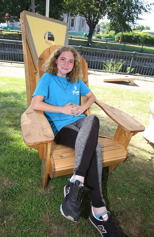 . Features at Friday afternoon Lowell Farmers Market. Bianka Close, 18, of Lowell, who is a culinary student with YouthBuild, sits in one of the Adirondack chairs that YouthBuild sells. Plain chairs like this are $140; stained are $145. (SUN/Julia Malakie)
