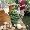 Features at Friday afternoon Lowell Farmers Market. Tom Malone of Lowell shops for vegetables at the Spring Brook Farm (of Littleton) booth. (SUN/Julia Malakie)